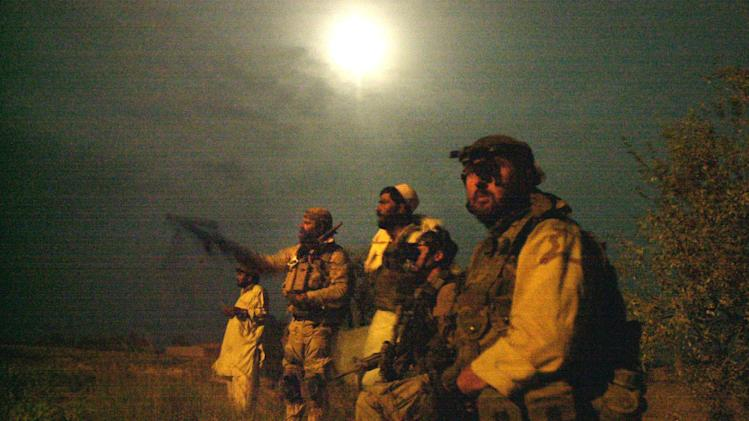 FILE - In this Aug. 24, 2002, file photo members of the U.S. Army Special Forces keep close eye on the moon-lit perimeter of a compound, suspected of holding al-Qaida and Taliban forces, during a raid on a compound home in Narizah, east of Kabul, Afghanistan, as part U.S. Special Forces' Operation Mountain Sweep. The Central Intelligence Agency together with U.S. special operations were the first Americans into Afghanistan after the attacks of Sept. 11th, and will likely be the last U.S. forces to leave. (AP Photo/Wally Santana, File)