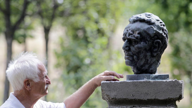 In this photo taken Monday, Aug. 27, 2012, Blasko Gabric, the owner of the Yugoland theme park, looks at a bust of late Yugoslavian communist dictator Josip Broz Tito which is on display at the park in the northern Serbian town of Subotica. The Yugoland theme park, for years a gathering spot for the admirers of the former communist state, faces closure because Gabric put up part of the property as collateral in a bank loan that went bad. (AP Photo/Darko Vojinovic)