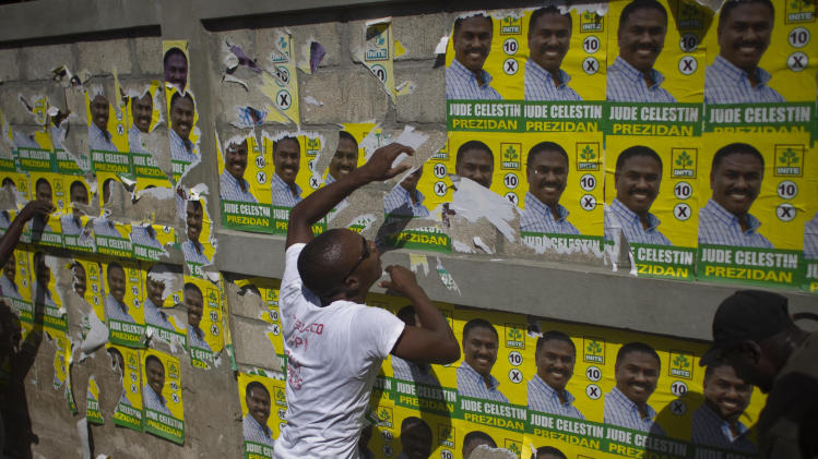 People remove electoral posters with images of presidential candidate Jude Celestin during a protest against the upcoming elections in Port-au-Prince, Haiti, Wednesday, Nov. 24, 2010. Haiti will hold elections on Nov. 28 in the midst of a month-old cholera epidemic that has killed at least 1,000 people and hospitalized thousands. (AP Photo/Ramon Espinosa)