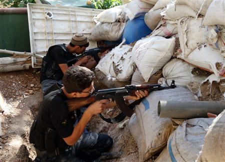 Free Syrian Army fighters take up positions behind piled sandbags as they aim their weapons in the eastern al-Ghouta, near Damascus September 8, 2013. REUTERS/Msallam Abd Albaset