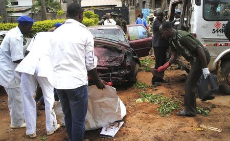 Workers pick items at the scene of a bombing in Kaduna