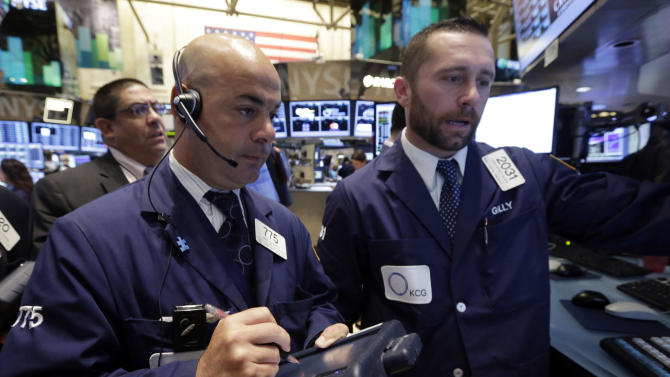 Trader Fred DeMarco, center, and specialist Christopher Gildea, right, on the floor of the New York Stock Exchange Monday, July 22, 2013. The stock market edged higher as a big week of earnings kicked off Monday, with mixed results from a handful of large U.S. companies. (AP Photo/Richard Drew)