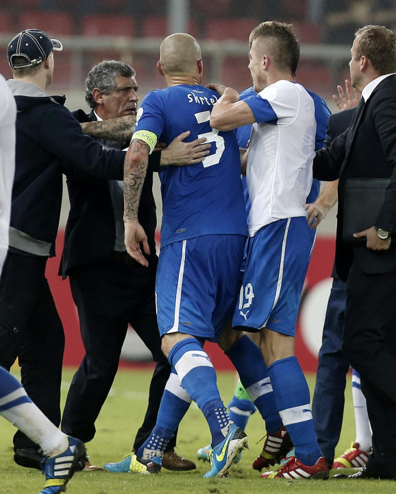 Greece's coach Fernando Santos from Portugal, second left, holds Slovakia's captain Martin Skrtel (3) as he tries to confront  a Greek player after their World Cup Group G qualifying soccer match at t