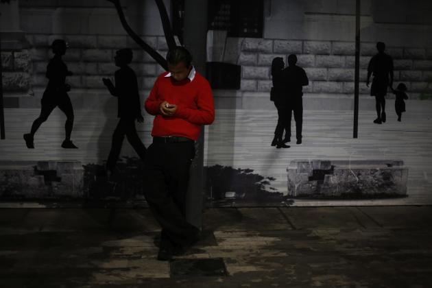 A man types a text message on his cell phone as he stands in front of a backdrop depicting a part of the Palace of Fine Arts in downtown Mexico City