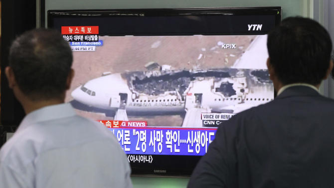 """People watch a news program reporting about Asiana Airlines flight 214 which took off from Seoul and crashed while landing at San Francisco International Airport, at Seoul Railway Station in Seoul, South Korea, Sunday, July 7, 2013. The writing on the screen reads """" Local media saying two people died."""" (AP Photo/Ahn Young-joon)"""