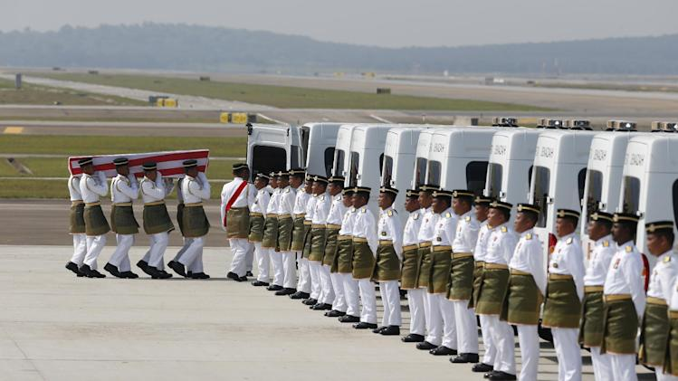 Malaysia Army soldiers carry a coffin containing one of the bodies of the downed MH17 flight, to load it to a hearse upon arrival at Kuala Lumpur International Airport in Sepang, Malaysia, Friday, Aug. 22, 2014. The bodies and ashes of 20 Malaysians killed when Malaysia Airlines Flight 17 was shot down over Ukraine in July have arrived in Kuala Lumpur, the first repatriation of victims from the flight to the country. (AP Photo/Vincent Thian)