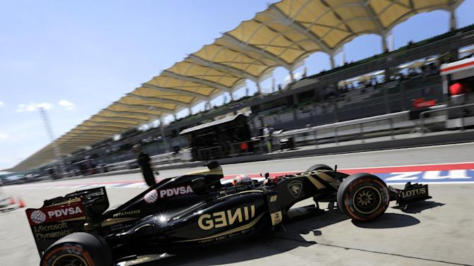 Lotus driver Romain Grosjean of France steers his car out of his team's garage during the first practice session for the Malaysian Formula One Grand Prix at Sepang International Circuit in Sepang, Malaysia Friday, March 27, 2015. (AP Photo/Andy Wong)