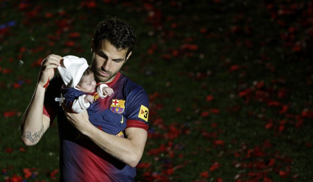 Barcelona's Cesc Fabregas holds his daughter Lia during the Spanish league first division trophy celebrations at Camp Nou stadium in Barcelona