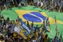 Supporters of presidential candidate of the Brazilian Social Democracy Party Aecio Neves rally as they hold a giant Brazilian flag in Belo Horizonte, Brazil, Saturday, Oct. 25, 2014. Neves and Brazil's President Dilma Rousseff, presidential candidate for re-election are in a tight election contest, that culminates Sunday when millions of Brazilians are expected to go to the polls and decide who'll be the next leader of Latin America's biggest economy. (AP Photo/Andre Penner)