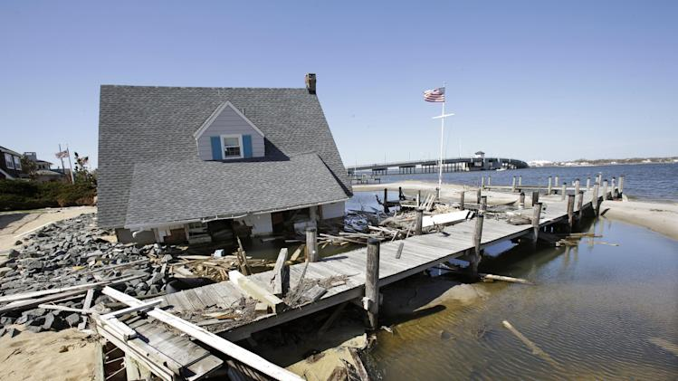 A home rests next to a pier in Barnegat Bay, Thursday, April 25, 2013, near the Mantoloking Bridge in Mantoloking, N.J., after it was swept away last October by Superstorm Sandy. Six months after Sandy devastated the Jersey shore and New York City and pounded coastal areas of New England, the region is dealing with a slow and frustrating, yet often hopeful, recovery. (AP Photo/Mel Evans)