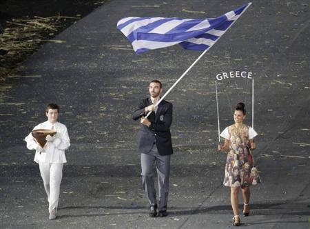 Greece's flag bearer Alexandros Nikolaidis holds the national flag as he leads the contingent in the athletes parade during the opening ceremony of the London 2012 Olympic Games at the Olympic Sta
