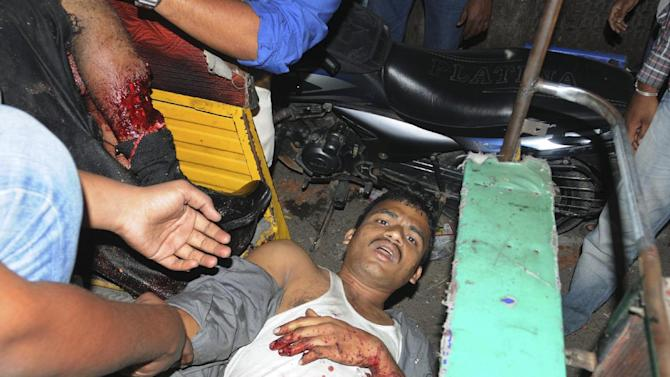 People rescue an injured person after a bomb blast in Hyderabad, India,Thursday, Feb. 21, 2013. Several people were killed and many injured Thursday in a pair of explosions in a crowded area of the southern Indian city of Hyderabad, officials said. (AP Photo)