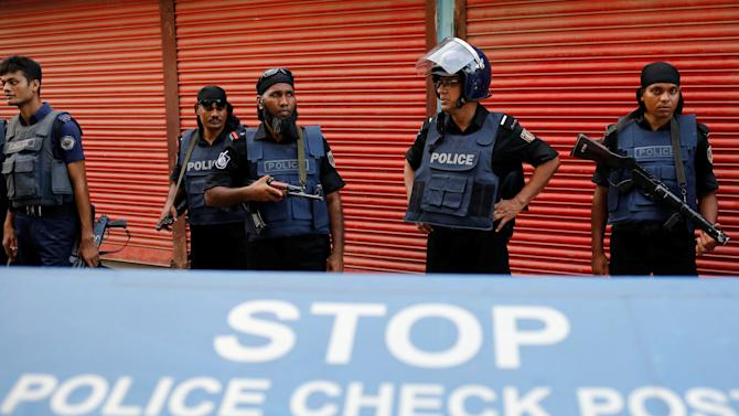 Police keep watch near the site of a gun battle on the outskirt of Dhaka