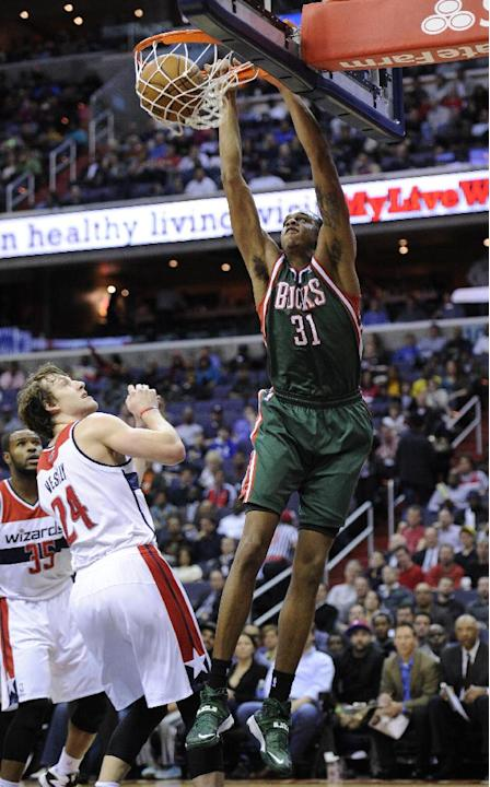 Milwaukee Bucks forward John Henson (31) dunks against Washington Wizards forward Jan Vesely (24), of the Czech Republic, and Trevor Booker (35) during the first half of an NBA basketball game on Frid