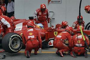 Fernando Alonso of Spain is attended to by his crew during a pit stop during the Brazilian F1 Grand Prix at the Interlagos circuit in Sao Paulo
