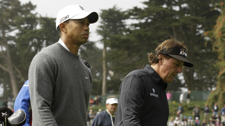 Phil Mickelson and Tiger Woods make their way to the 18h hole during the first round of the U.S. Open Championship golf tournament Thursday, June 14, 2012, at The Olympic Club in San Francisco. (AP Photo/Charlie Riedel)