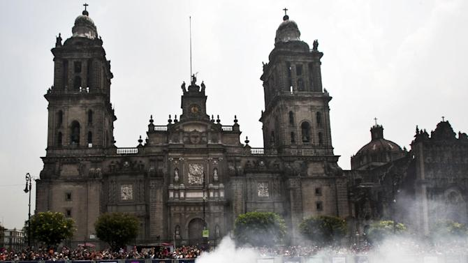 A Redbull driver rolls past the Metropolitan Cathedral during a Formula One exhibition in Mexico City's main plaza, the Zocalo, Saturday, June 27, 2015. Mexico last held an F1 race in 1992 at Autodromo Hermanos Rodriguez in Mexico City, the venue for the November 1 race. (AP Photo/Marco Ugarte)