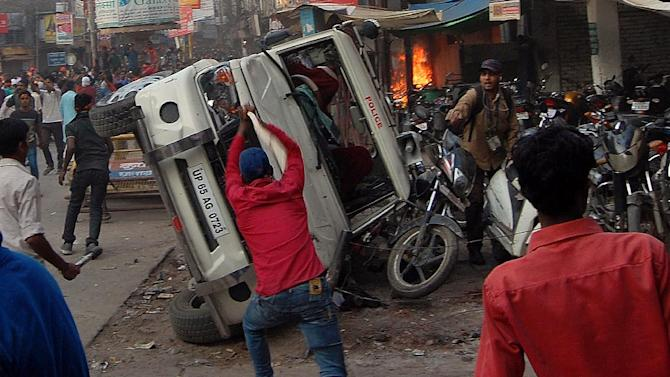 Indian protesters overturn a police jeep during clashes between sadhus - holy men - and police in Varanasi on October 5, 2015