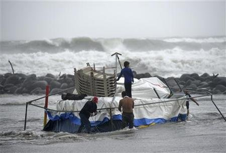 People try to salvage furniture of their food stand as it is being washed away by flood in Boca Del Rio on the outskirts of Veracruz