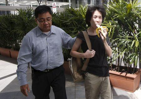 Amos Yee eats a banana as he arrives with his father to the State Courts for a pre-trial conference in Singapore