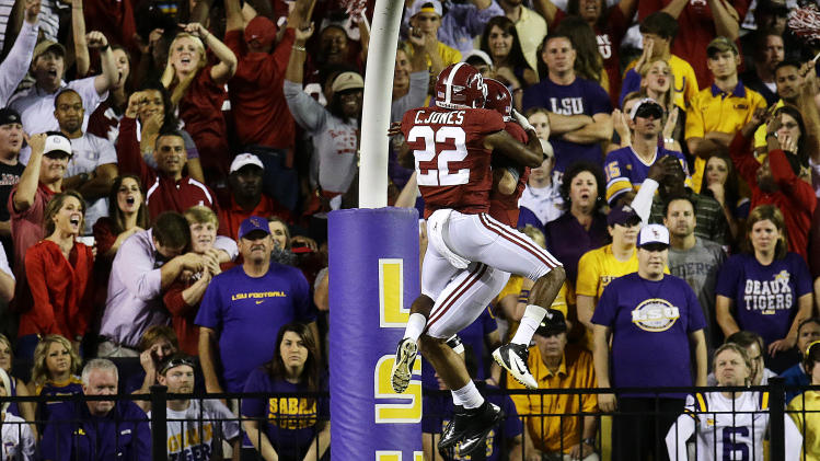 Alabama fans, left, and LSU fans, right, reacts as Alabama quarterback AJ McCarron (10) celebrates his rushing touchdown with wide receiver Christion Jones (22) in the first half of their NCAA college football game in Baton Rouge, La., Saturday, Nov. 3, 2012. (AP Photo/Bill Haber)