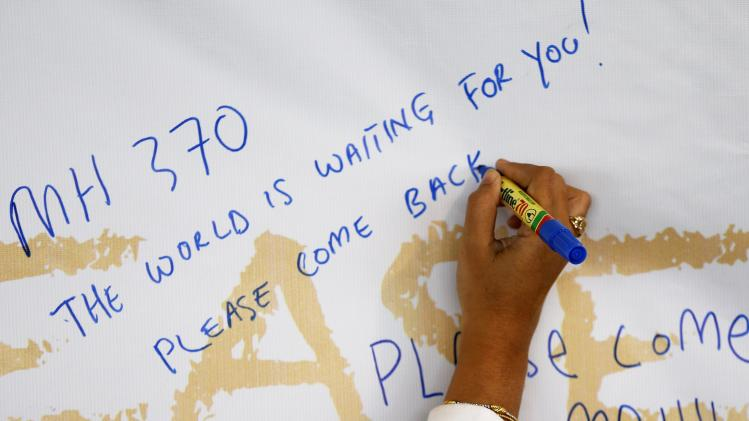 A woman writes messages of support and hope for the passengers of the missing Malaysia Airlines MH370 at Kuala Lumpur International Airport