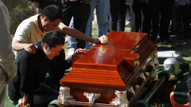 Family members mourn in front of a coffin containing the remains of Eva Melchor, a victim of the Mexico oil company office building explosion, at a cemetery in Mexico City, Saturday, Feb. 2, 2013.  Melchor died Thursday, in a blast that collapsed the lower floors of Petroleos Mexicanos, or Pemex, headquarters,  crushing at least 33 people beneath tons of rubble and injuring 121. (AP Photo/Marco Ugarte)