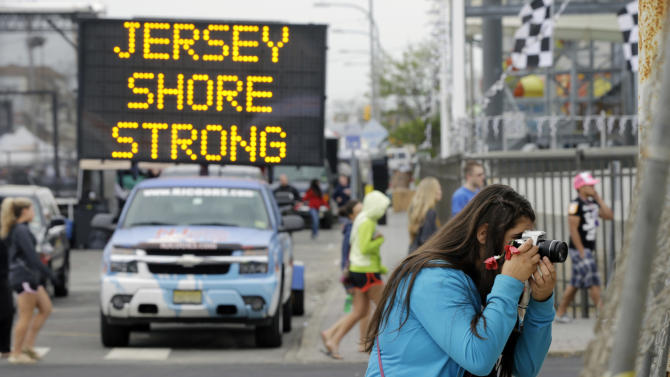 Angelina Zuzuro, 16, of Denville, takes photos near a sign in Seaside Heights, N.J., Saturday, May 18, 2013. The boardwalks are back, and so are most of the beaches, even if some are a little thinner this year. The smell of funnel cakes, french fries and pizza will mingle with the salt air, and the screech of seagulls will be heard. But so will the thwack of hammers repairing what can be fixed and the roar of bulldozers and backhoes tearing down what can't. Welcome to Summer 2013 at the Jersey shore, the first since Superstorm Sandy pummeled the coast and upended hundreds of thousands of lives. (AP Photo/Mel Evans)
