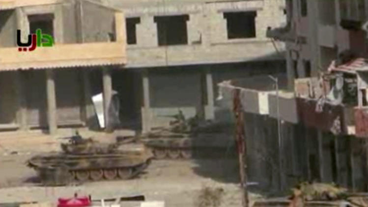 In this image taken from video obtained from the Sham News Network, which has been authenticated based on its contents and other AP reporting, a pair of what activists say are tanks from President Bashar Assad regime in sit in a street in the Daraya neighborhood of Damascus, Syria, just before one of them fires a shot Friday, Jan. 25, 2013. Troops battled rebels around Damascus in an effort to dislodge opposition fighters who have set up enclaves around the capital, including Daraya and Zabadani. (AP Photo/Sham News Network via AP video)