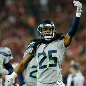 Seattle Seahawks cornerback Richard Sherman intercepts San Francisco 49ers quarterback Colin Kaepernick