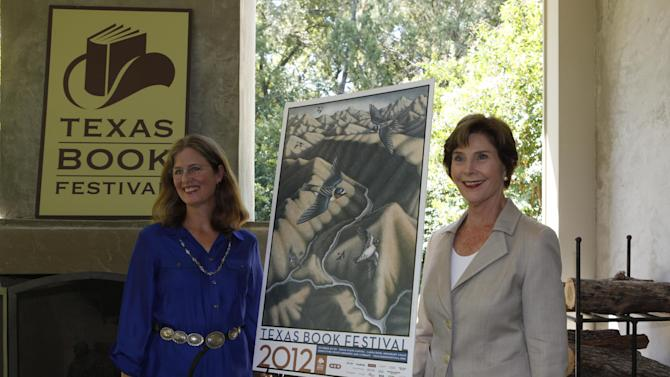 Former first lady Laura Bush, right, and artist Margie Crisp posses with the poster that Crisp made for the 2012 Texas Book festival Wednesday, Sept. 12, 2012, at Bush's home in the Preston Hollow section of Dallas.  Bush, who founded the festival when she was first lady of Texas, unveiled this year's book festival poster for the annual event in Austin. (AP Photo/LM Otero)