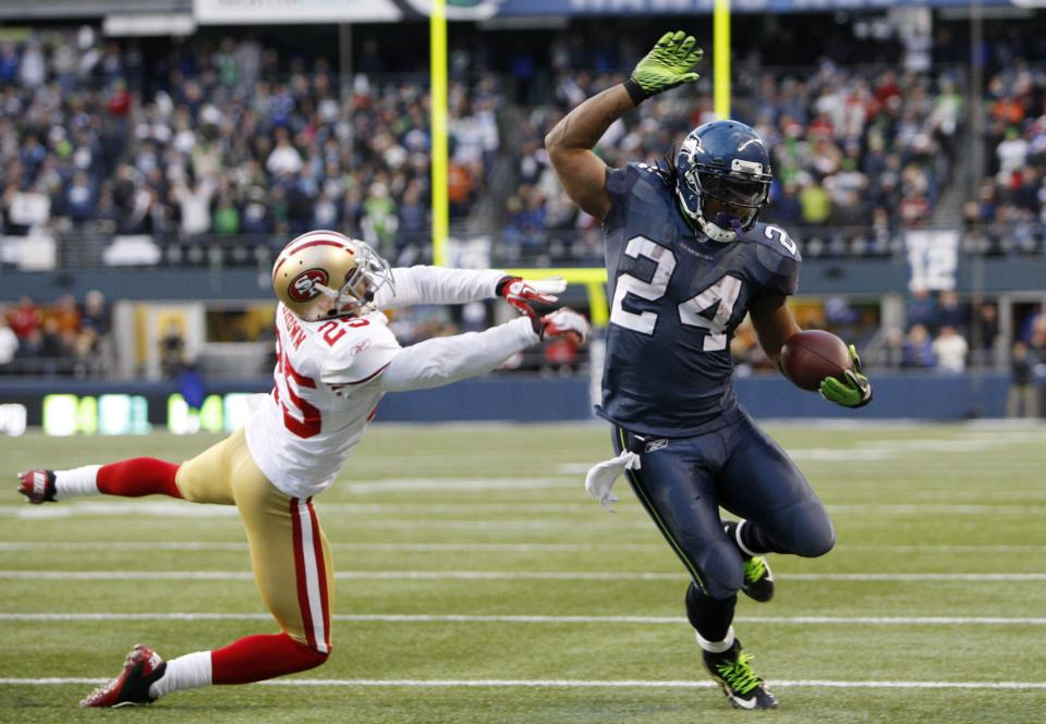 Seattle Seahawks'  Marshawn Lynch scores on a run as San Francisco 49ers'  Tarell Brown defends in the second half of an NFL football game Saturday, Dec. 24, 2011, in Seattle. (AP Photo/Kevin Casey)