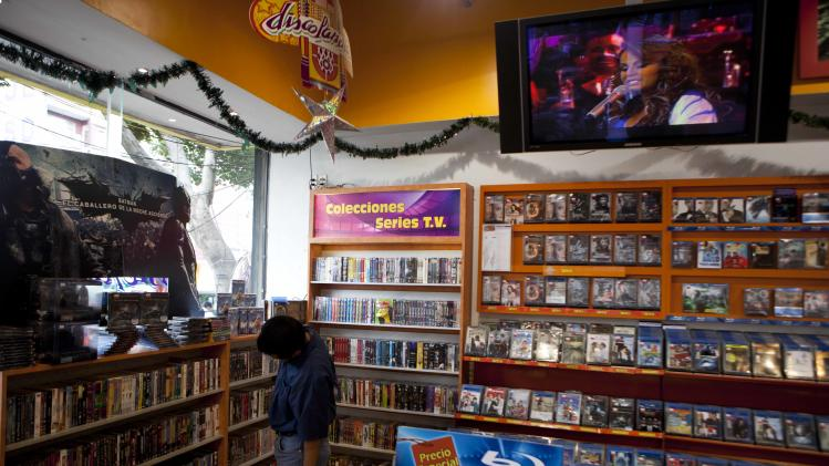 Singer Jenni Rivera is seen on a video screen, top, at a music store in Mexico City, Monday, Dec. 10, 2012. U.S. authorities confirmed Monday that Rivera, a U.S.-born singer whose soulful voice and openness about her personal troubles made her a Mexican-American superstar, was killed in a plane crash early Sunday in northern Mexico. (AP Photo/Eduardo Verdugo)