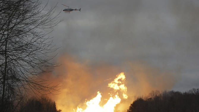 A helicopter files above flames from a gas line explosion across Interstate 77 near Sissonville, W.Va., Tuesday, Dec. 11, 2012. At least five homes went up in flames Tuesday afternoon and a badly damaged section of Interstate 77 was shut down in both directions near Sissonville after a natural gas explosion triggered an hour-long inferno that officials say spanned about a quarter-mile.  (AP Photo/Joe Long)