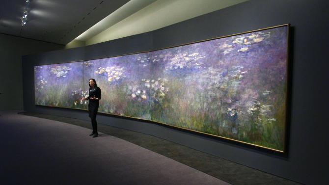 """Nicole Myers, Associate Curator of European Painting and Sculpture at the Nelson-Atkins Museum of Art, talks about Claude Monet's """"Water Lilies"""" triptych during a press preview of the exhibit, Friday, April 1, 2011, in Kansas City, Mo. For the first time in 30 years the three panel work of the Impressionist artist will be on display at the museum and will run from April 9 through August 7, 2011. (AP Photo/Ed Zurga)"""