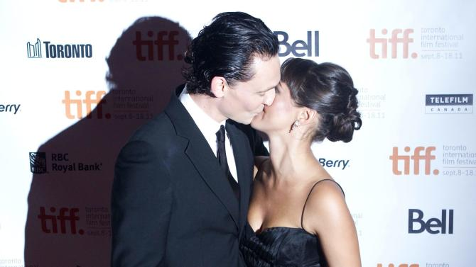 """Tom Hiddleston, left, kisses his wife Susannah Fielding as they arrive for the gala screening of the film """"The Deep Blue Sea"""" at the Toronto International Film Festival in Toronto, Sunday, Sept. 11, 2011. (AP Photo/The Canadian Press, Chris Young)"""