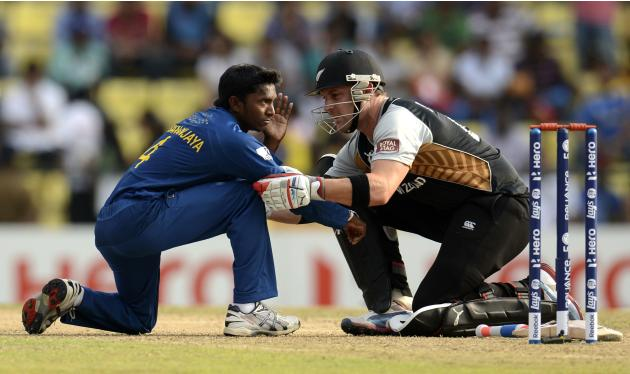 Sri Lanka's Dhananjaya is helped by New Zealand's McCullum after being hit in the face by the ball during the Twenty20 World Cup Super 8 match at Pallekele in Sri Lanka