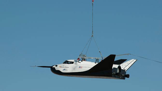 In this Aug. 22, 2013 photo made available by NASA, the Sierra Nevada Corporation's Dream Chaser spacecraft is carried by a helicopter during a test in Sparks, Nev. On Saturday, Oct. 26, 2013, the Nevada-based company tested a full-scale model at Edwards Air Force Base in California in its first free flight, but after being dropped by a helicopter, the left landing gear deployed too late and the test vehicle skidded off the runway. (AP Photo/NASA, Carla Thomas)