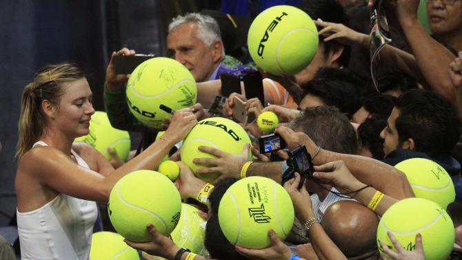 Sharapova of Manila Maverickcs team signs an autograph for a fan on a large tennis ball after beating Mladenovic of the UAE Royals team in their women's singles tennis match at the IPTL competition in Manila