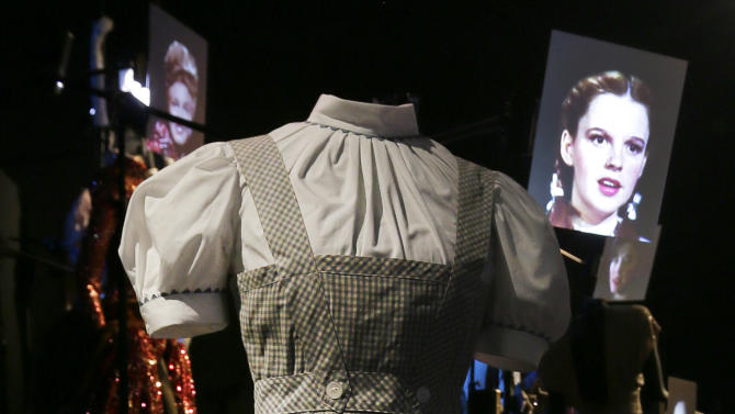 """In this Tuesday, Oct. 16, 2012 photo, the blue-and-white gingham pinafore dress worn by Judy Garland in her iconic role of Dorothy designed by Adrian for the 1939 film """"The Wizard Of Oz,"""" with a video portrait of garland in the background, appears on display at the Hollywood Costume exhibition at the Victoria and Albert museum in London. On Sunday, Nov. 11, 2012, auction house Julien's Auctions said the gingham dress fetched the highest price of any item during a two-day auction of Hollywood memorabilia that attracted bids from around the world, selling for $480,000. (AP Photo/Alastair Grant)"""