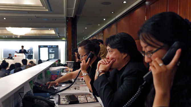 Staff members listen to collectors' offers on the phone during the autumn sale of China Guardian Auctions Co., in Hong Kong Sunday, Oct. 7, 2012. Chinese and international auction houses are encroaching on each other's territory in Hong Kong and Beijing for the first time this autumn sale season as they step up the battle for the Asian art market. (AP Photo/Vincent Yu)