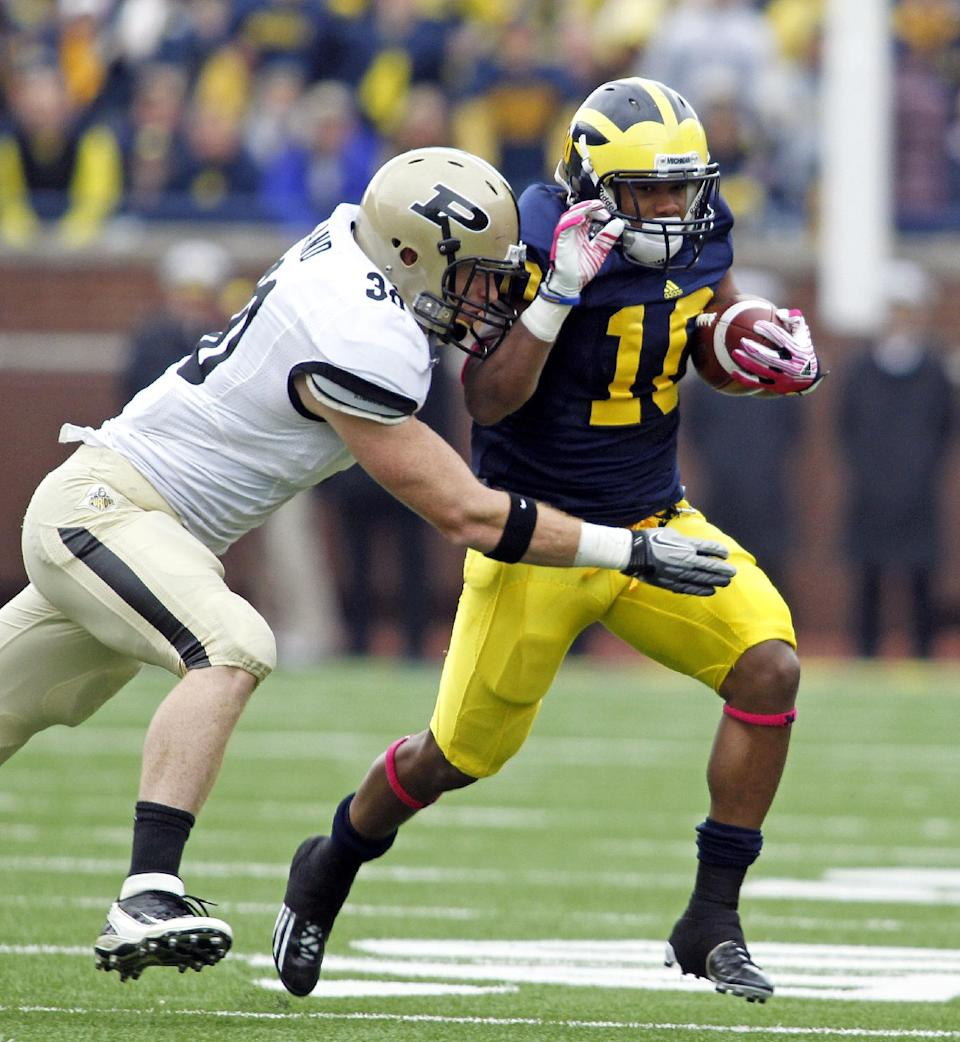 Purdue linebacker Joe Holland (30) tries to tackle Michigan wide receiver Jeremy Gallon (10) in the first quarter of an NCAA college football game, Saturday, Oct. 29, 2011, in Ann Arbor, Mich. (AP Photo/Tony Ding)