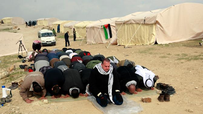Palestinian activists pray in the new 'outpost settlement' of Bab al-Shams (Gate of the Sun) in an area known as E1, near Jerusalem, Friday, Jan 11, 2013. Palestinian activists pitched tents in the West Bank on Friday to protest Israeli plans to build a large Jewish settlement on a key route through the territory. The E-1 settlement would block east Jerusalem from its West Bank hinterland — both territories captured by Israel during the 1967 Mideast war. (AP Photo/Majdi Mohammed)