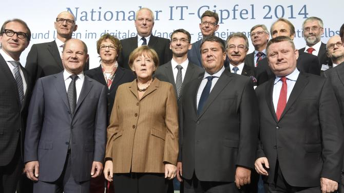 "German Chancellor Merkel pose with participants for a group photo at the ""National IT Summit"" in Hamburg"