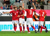 Park Jong-Woo (L) celebrates with teammates after scoring against Uzbekistan&#39;s national U-23 team during a match in Seoul in 2011. He will be excused military service despite controversially displaying a sign on a territorial dispute at the Olympic Games, the head of conscription said on Friday