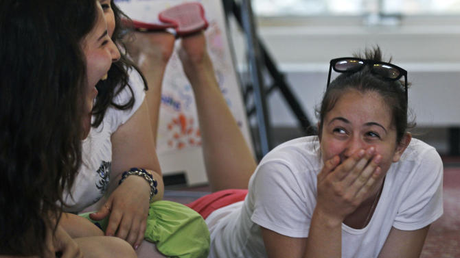 "Amina Sabanova, of Russia, right, laughs with Alla Nogaeva, of Russia, while attending the ""Common Bond"" summer camp in Newbury, Mass., Wednesday, July 18, 2012.  Teens from across the world who lost loved one due to terrorism gathered for the 10 day camp to share their feelings, insights and a chance to be the world's next generation of international peacemakers. Both girls lost family members in a school hostage crisis in Beslan, Russia during 1994 where more than 350 were killed. (AP Photo/Charles Krupa)"