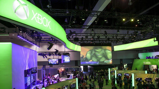 FILE - In a June 5, 2012 file photo attendees walk past Microsoft XBox booth at Electronic Entertainment Expo 2012 in Los Angeles. At E3 this year about 46,000 attendees are expected to play, poke and prod new video games and gizmos from more than 200 exhibitors. (AP Photo/Damian Dovarganes, file)