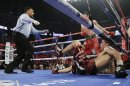 Sergio Martinez falls to the mat as referee Tony Weeks directs Julio Cesar Chavez Jr. to his corner in the 12th round during the WBC middleweight title fight, Saturday, Sept. 15, 2012, in Las Vegas. Martinez won by unanimous decision. (AP Photo/Julie Jacobson)