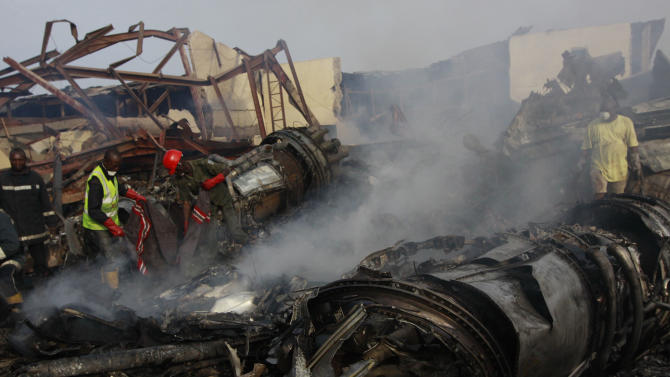 Rescue workers search for  bodies at the site of a plane crash in Lagos, Nigeria, Monday, June 4, 2012. A passenger plane carrying more than 150 people crashed in Nigeria's largest city on Sunday, government officials said. Firefighters pulled at least one body from a building that was damaged by the crash and searched for survivors as several charred corpses could be seen in the rubble.(AP Photo/Sunday Alamba)
