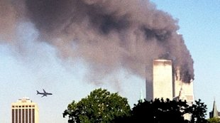 A hujacked airliner makes straight for the World Trade Center even as one of the Twin Towers burns
